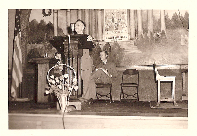 In a rental for either a zone or circuit assembly; George Zimmerman at lectern with American flag to his right (from Ray and Marilyn Marsh's collection)
